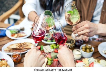 Hands with glasses of wine and tasty food