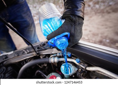 Hands in gloves holding bottle with non-freezing washer fluid and pouring it into windshield washer tank in winter. Replacement technical fluids according to season. Washer reservoir completely filled