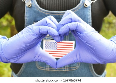 Hands in gloves with love gesture on focus and the US flag on the clothes of a lady in the background