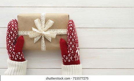 Hands in gloves, mittens holding Christmas present, gift box  with white cotton lace bow and ribbon on white wooden table. New Year, winter birthday. Christmas  concept.Top view with space for text.