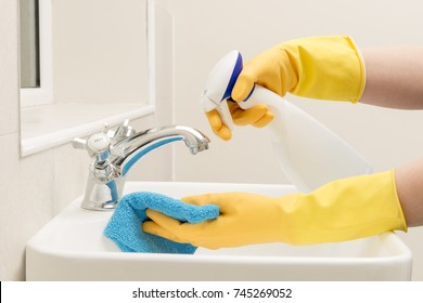 Hands in gloves spraying liquid soap on a rag for cleaning bathroom sink