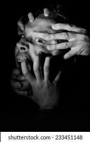Hands Grabbing a Head in the Dark
