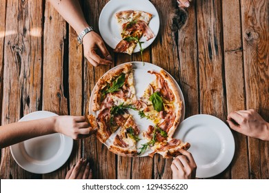 Hands grabbing pizza carbonara on rustic wooden table. Food photography concept. Top view