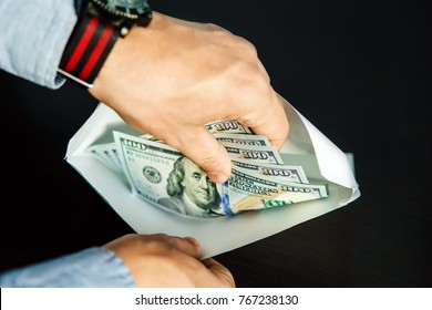 hands of grafter. He take US dollars from white envelope. Bribe-taker the brown wooden table. The employee believes illegal payment in a white envelope. Black salary