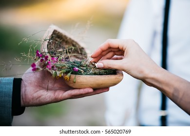 Hands of groom and bride close up take from wooden casket in heart form with grass, flowers in wedding rings to put on them each other during oath pronunciation on registration of marriage at wedding