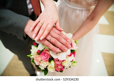 Hands of the groom and bride with golden rings