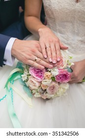 Hands of groom and bride on a blue wedding bouquet