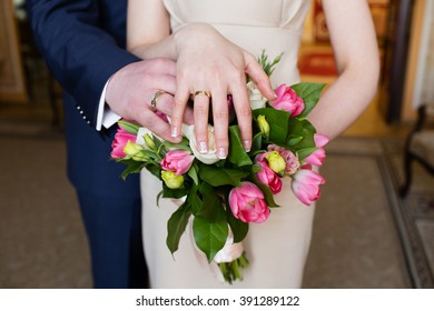 Hands of the groom and bride with rings and bridal bouquet