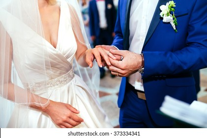 Hands of the groom and bride is wearing a ring on the finger on the day of the wedding ceremony. Gold, symbol, religion, love.