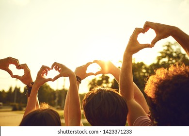 Hands of group friends in the shape of a heart against the sunset.