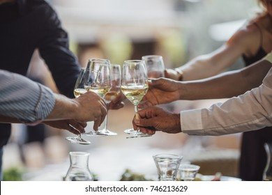 Hands of group of people cheering with wine at outdoor celebration.