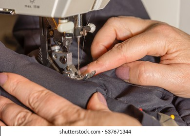 Hands guiding the cloth in a sewing machine