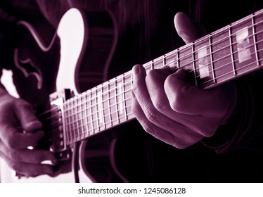 hands of guitarist playing an electric guitar,pink colr image