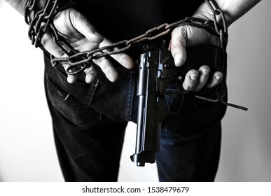Hands with gun in old rusty chains. Robber arrested for illegal crime. Mugger broken the law.