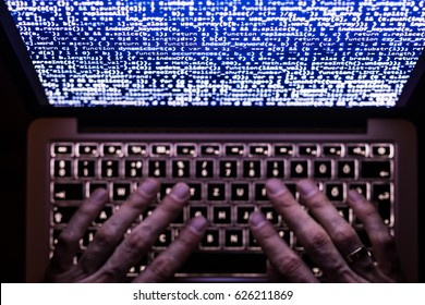 Hands of a hacker working on a laptop with a program screen