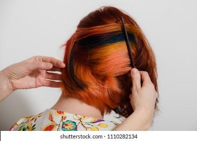 Hands of hairdresser making modern hairstyle on short hair