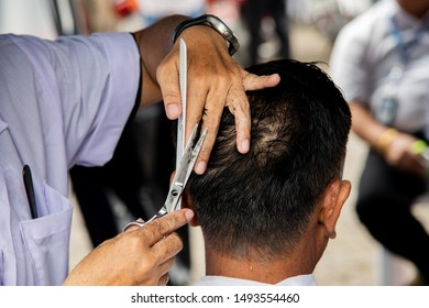 Hands of hairdresser use comb and scisscors doing haircut in communiter center.