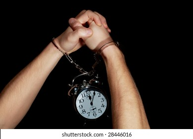 Hands in handcuffs with a clock