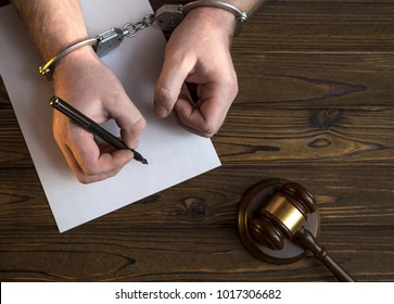 Hands in handcuffs and a hammer of the judge. writes on a sheet of paper, a police report, an explanation. The concept of committing and punishing, the law, the court.