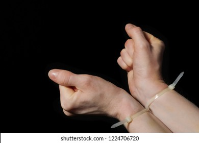 Hands in handcuffs, plastic zip tie on a black background. Big bruise. Attempt to break free from the shackles.