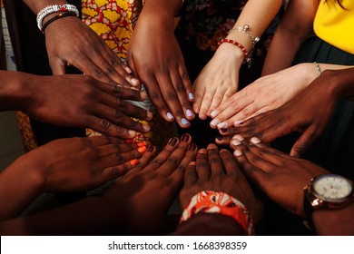 Hands of happy group of African Latin American and European people which stay together in circle