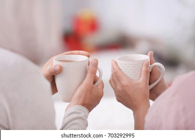 Hands of happy senior couple drinking hot tea at home. Christmas concept