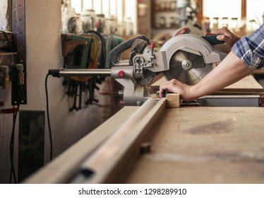 Hands of hard working woodworker sawing a piece of wood with a mitre saw in woodworking studio