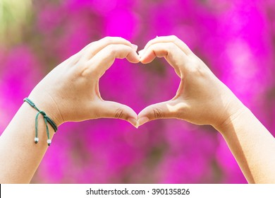Hands as a hart shape with pink background