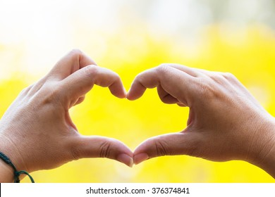 Hands as a hart shape with yellow background