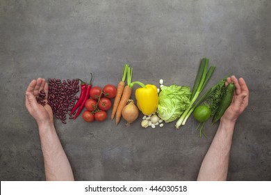 Hands harvesting fresh vegetables. Top view on man hands, vegetables on grey kitchen table. Flat lay food concept.