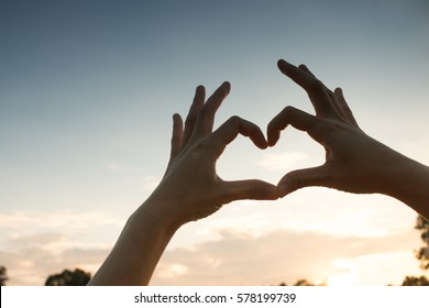 Hands in heart form love, silhouette hand make heart form with sun set.