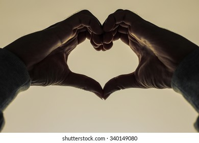 Hands in heart form love with sky background.