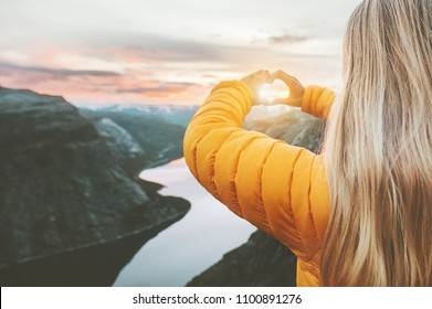 Hands heart love symbol shaped woman traveling lifestyle charity help concept vacations in Norway sunset mountains and lake landscape