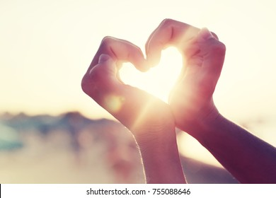 Hände in Herzform, die Sonnenuntergang am Strand