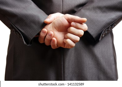 hands held behind the back of a suited man