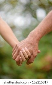 Hands held together on a background of nature