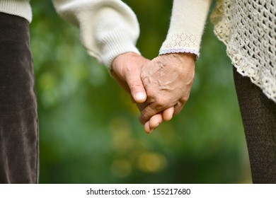 Hands held together on a natural green