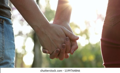 Hands held together with sunlight flare in the background