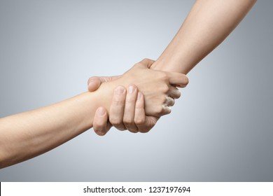 Hands helping each other on grey background