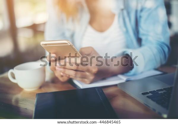 Hände von Hipster-Frau, die Smartphone in der Kaffeehalle mit weichen Retro-Ton.mit Reflexion von Fenstern