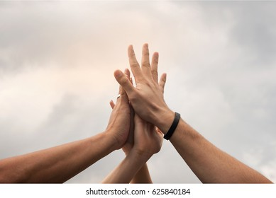 Hands hit and join together in to sky,after everybody success something that they do, example win in game,success in business,market up volume sales.symbolizing to trust each other.