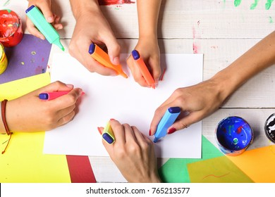 Hands hold colorful markers and draw, top view. Markers in male and female hands draw on blank white paper. Artists wooden table with paints and colored paper, copy space. Creativity and art concept