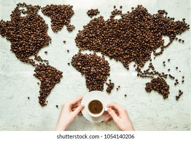 Hands hold a cup of coffee against the background of the world map from coffee beans