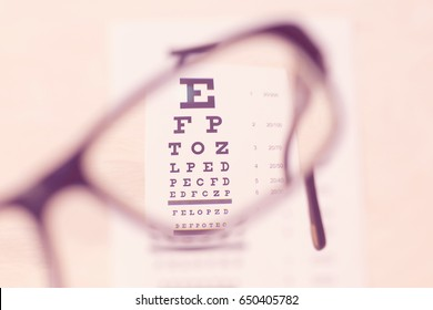 Hands hold eye glasses through table of check of vision