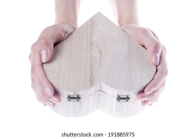 Hands hold heart shaped wooden gift box isolated on white
