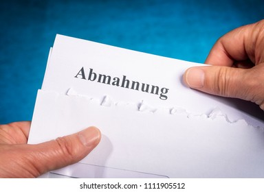 """Hands hold a letter with the german word """"Abmahnung"""" for a warning letter"""