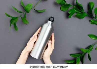 Hands hold metal bottle. Zero waste concept with green leaves on dark gray background.