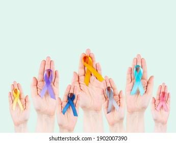 Die Hände haben mehrfarbige Bänder, Symbol des Kampfes gegen Krebs. Weltkrebstag