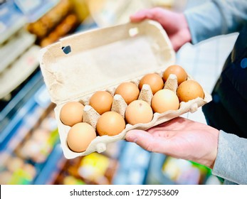 Hands hold a set of chicken eggs. Supermarket. Mobile photo.