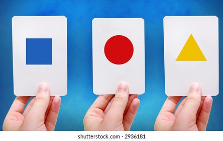 Hands hold up simple shapes on flash cards
